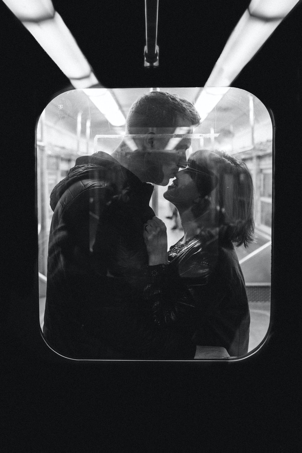 couple standing on window in grayscale photography