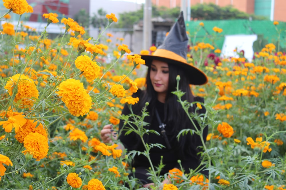 woman wearing black and yellow witch costume walking on yellow meadow flower