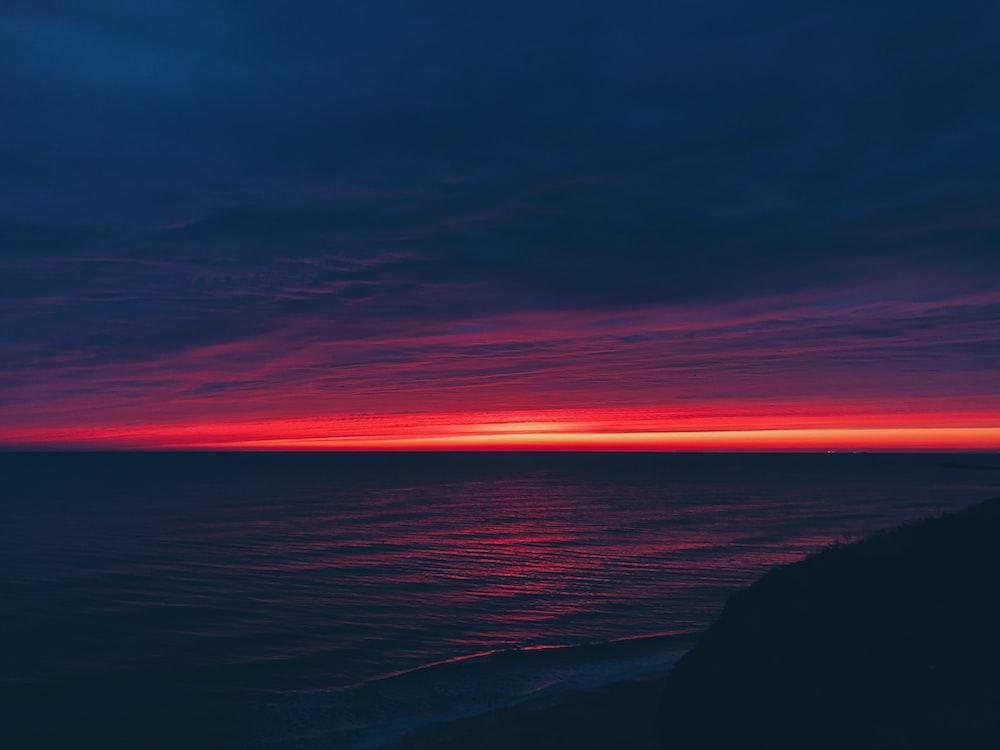 calm body of water during horizon