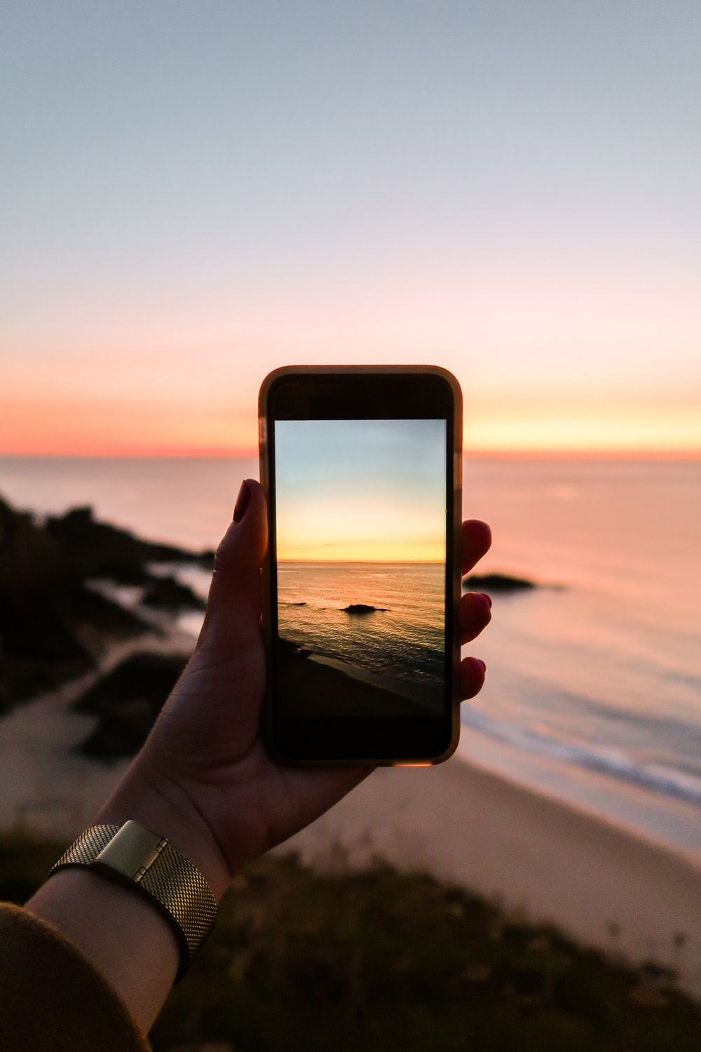 person holding smartphone taking photo of sea