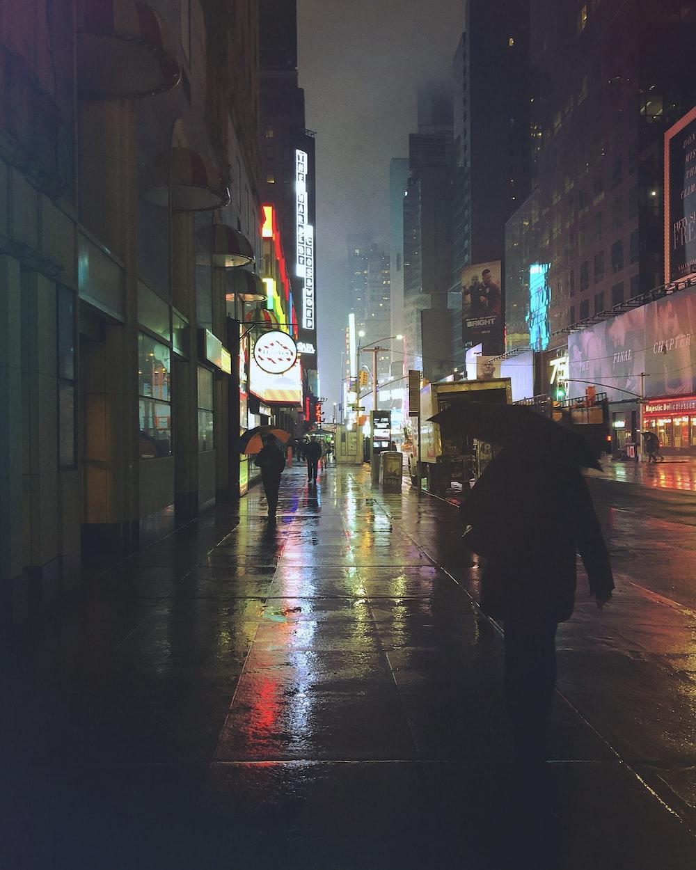 people walking on sidewalk at night