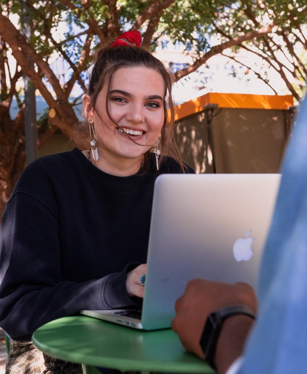woman smiling wearing black crew-nek sweater