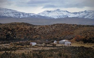 white concrete houses beside mountain patagonia teams background
