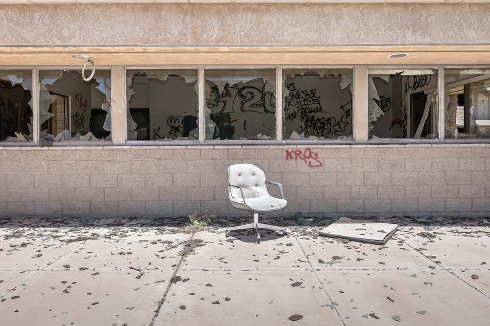 white rolling chair outside near abandoned builtind