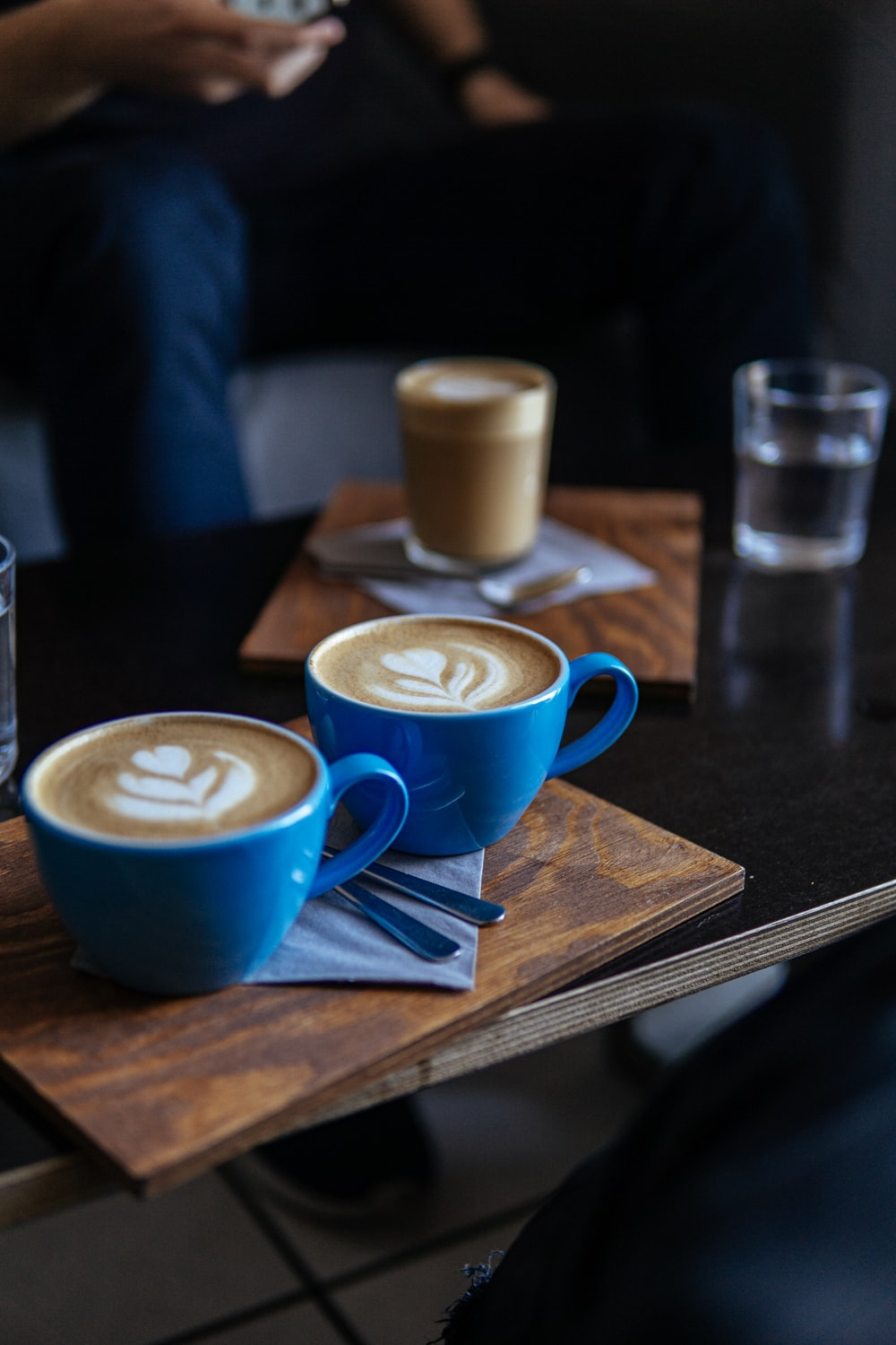 two blue ceramic mugs on brown table