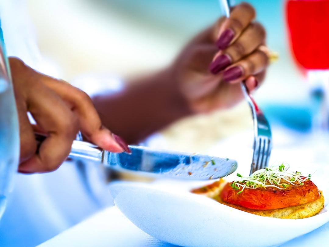A Woman eats gourmet Vegan food on the beach during sunset.