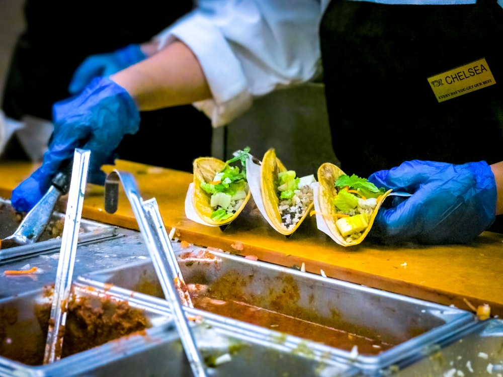 person about to put sauce on tacos