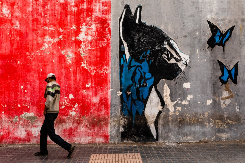 man walking on the street with graffiti on wall