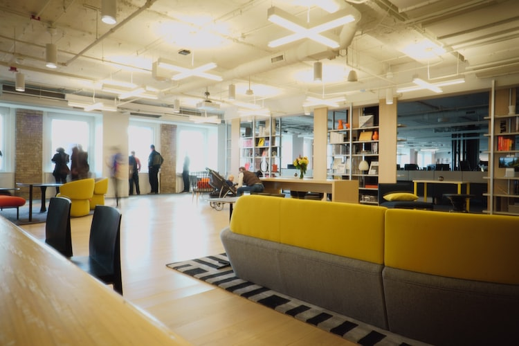 Industrial office lights and all workers crowded around large windows letting in natural light