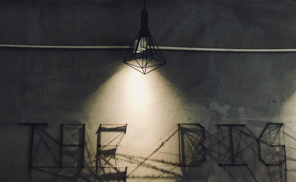 black pendant lamp and gray concrete wall