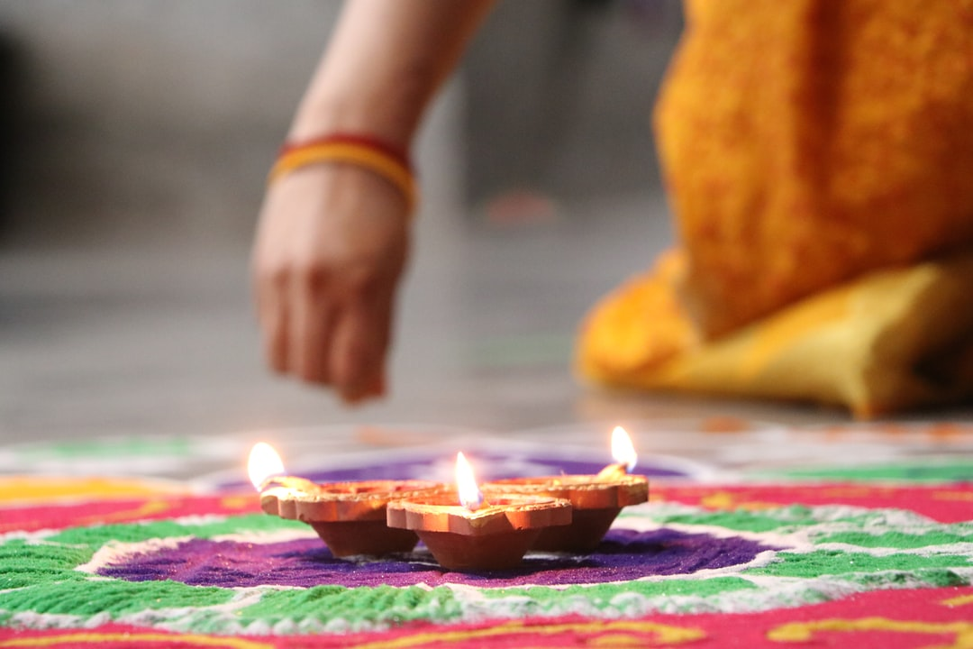woman creates intricate sand drawing around a candles during Diwali.