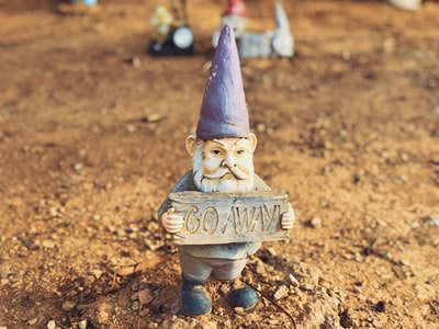 """A small garden gnome holding a sign that says """"go away!""""."""