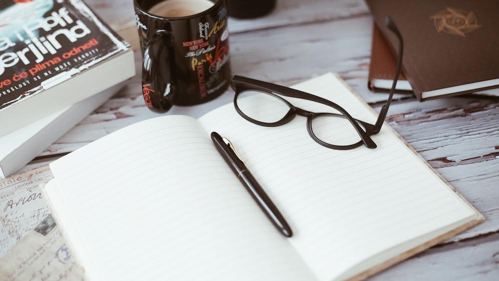 black-framed eyeglasses on book