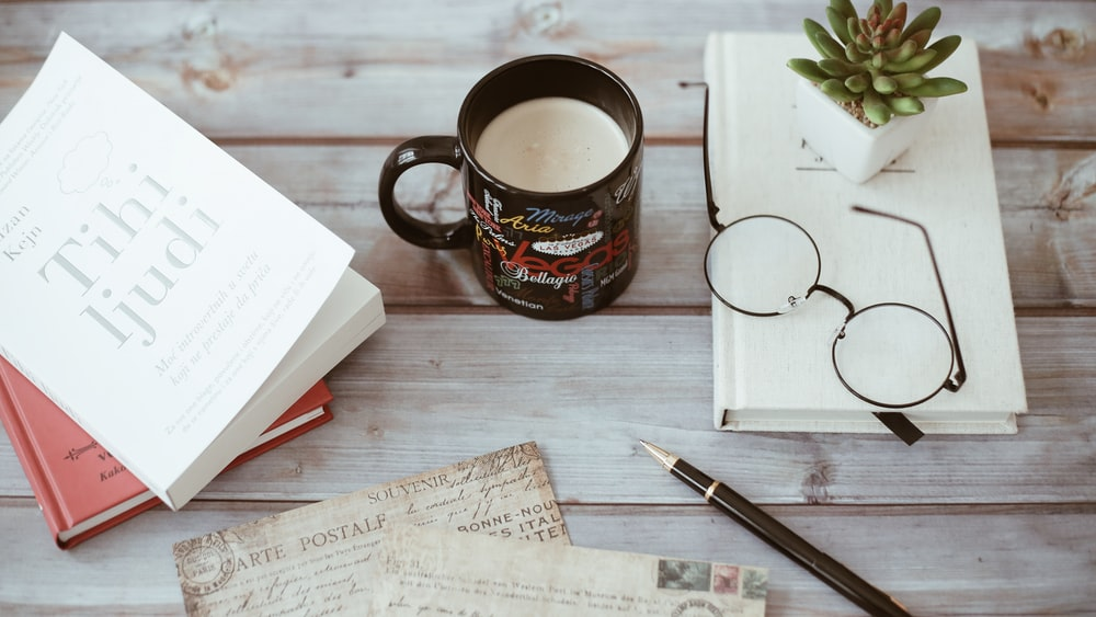 black and multicolored ceramic mug with white liquid beside papers, book, and eyeglasses