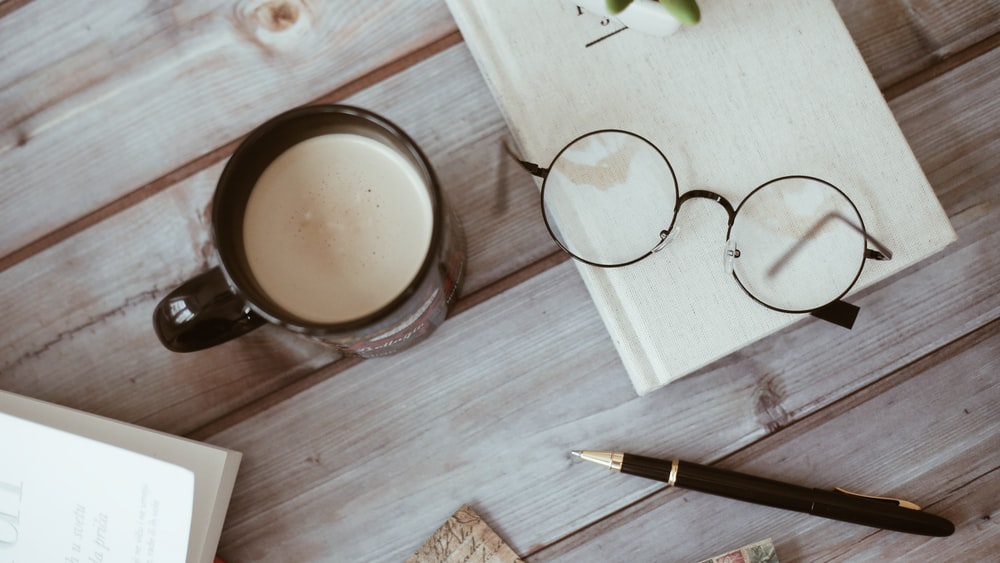 a cup of coffee near pen and eyeglasses