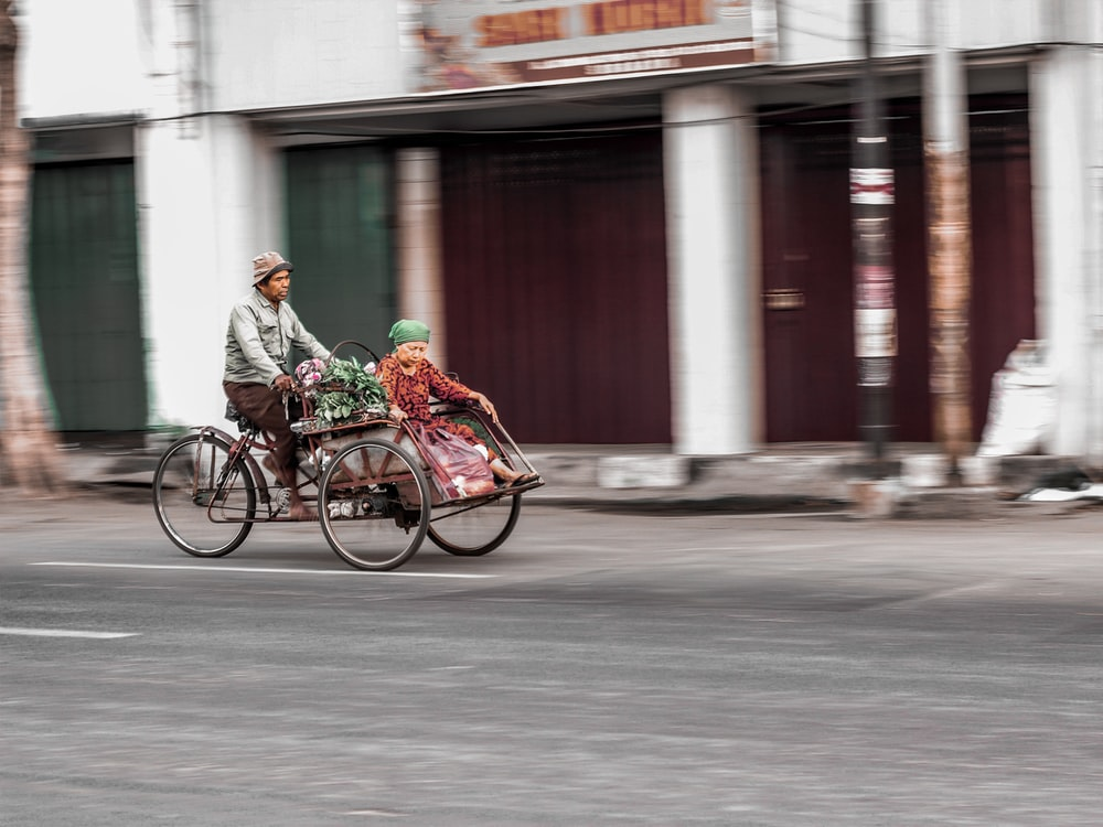 man riding trike with woman
