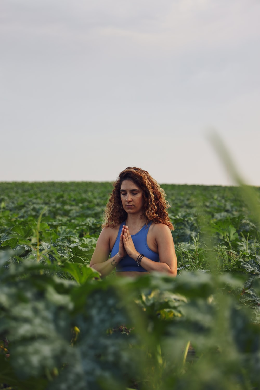 selective focus photography of woman meditating while sitting on ground surrounded by plants