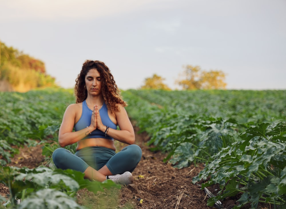woman sitting on ground while meditating and surrounded by plant field in macro photography