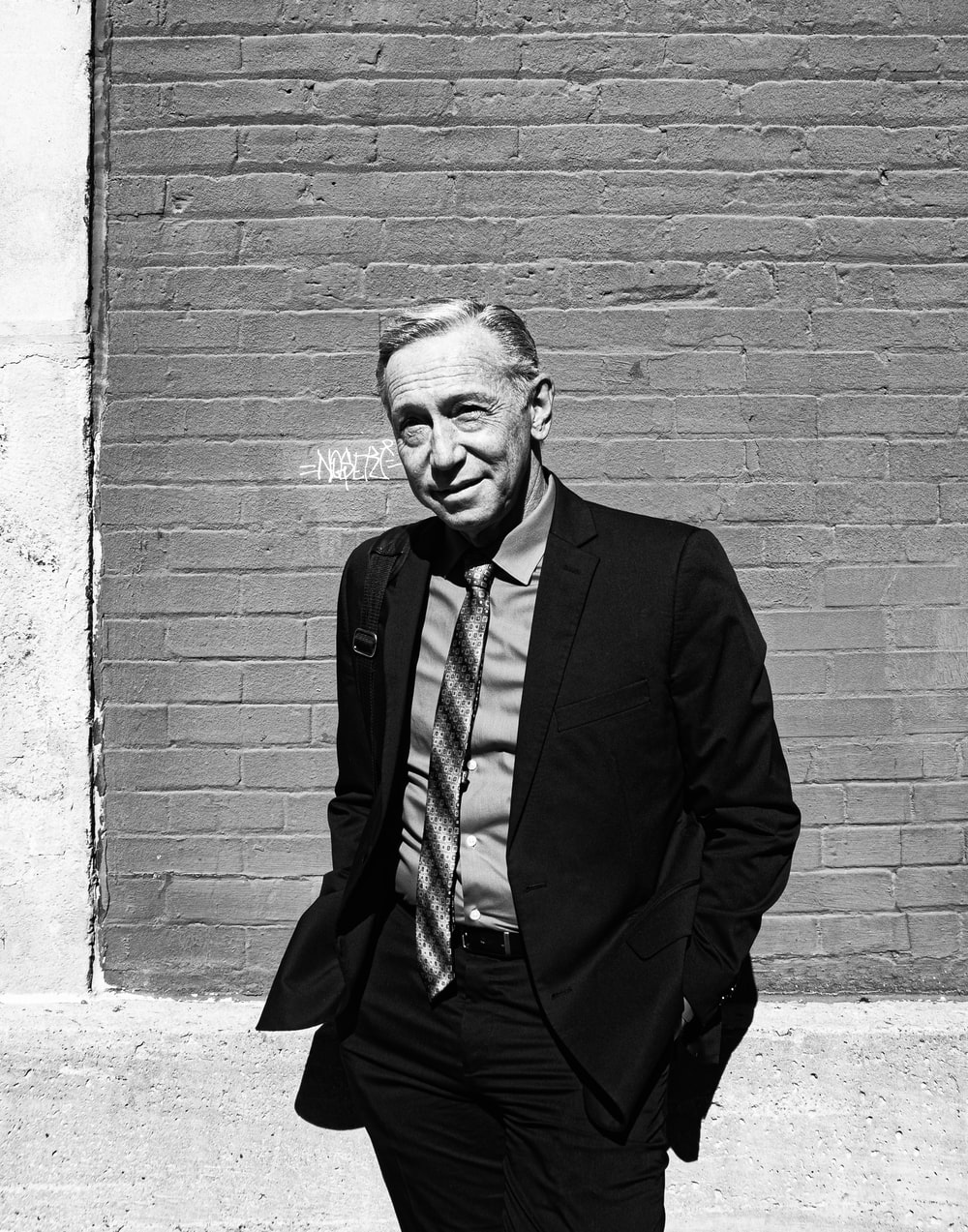 greyscale photo of man in suit