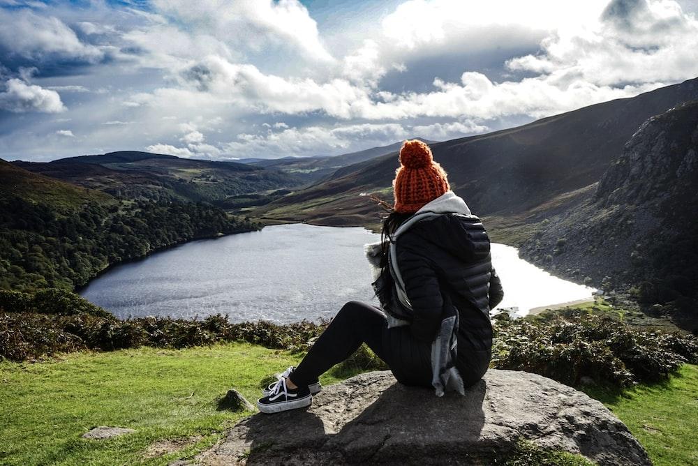 woman wearing black jacket sitting on rock