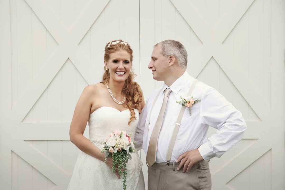 Rustic barn wedding in Sheboygan Falls, the bridal couple pose for formal portraits and this image catches the groom admiring his beautiful bride, who is radiantly smiling with joy and happiness in a gorgeous ivory wedding dress with succulent bouquet.