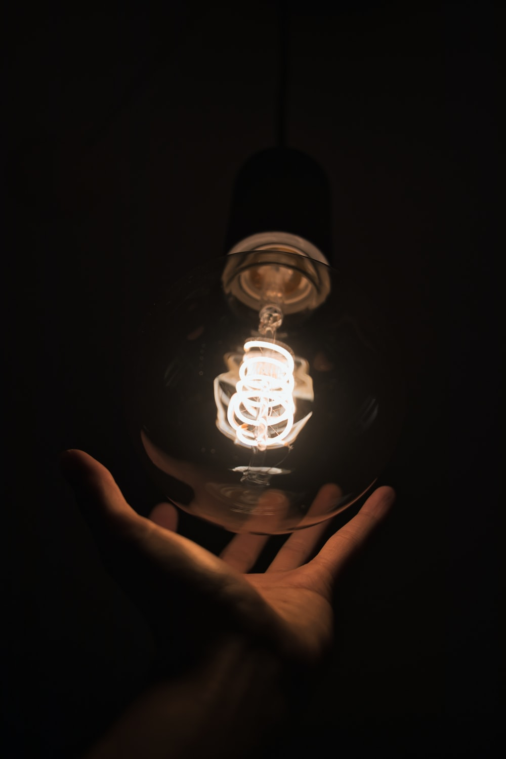 person touching light bulb