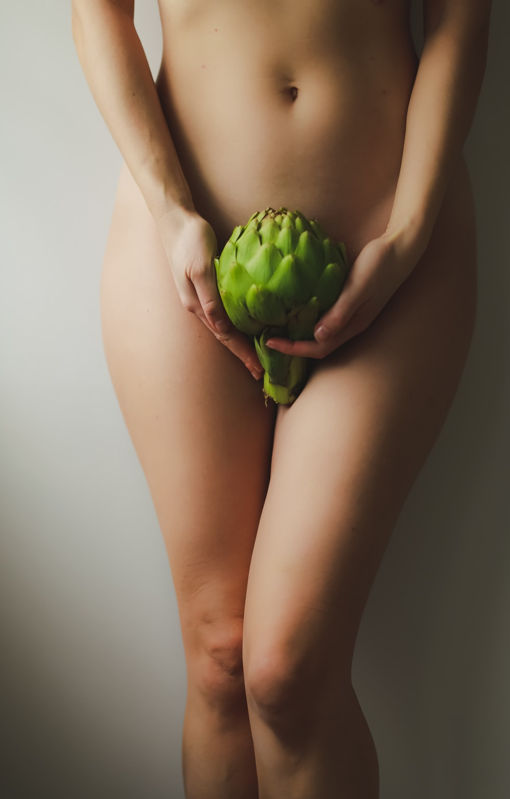 naked woman holding green fruit