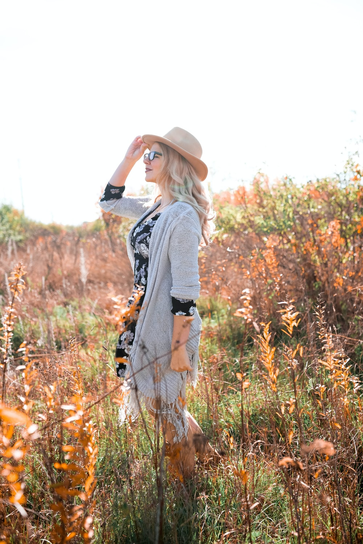 woman in open cardigan standing on grassy field