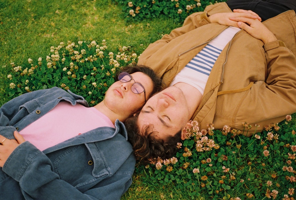 two man lying on grass with flowers