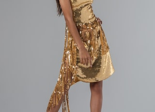 woman wearing gold deep V-neck sleeveless mini dress standing