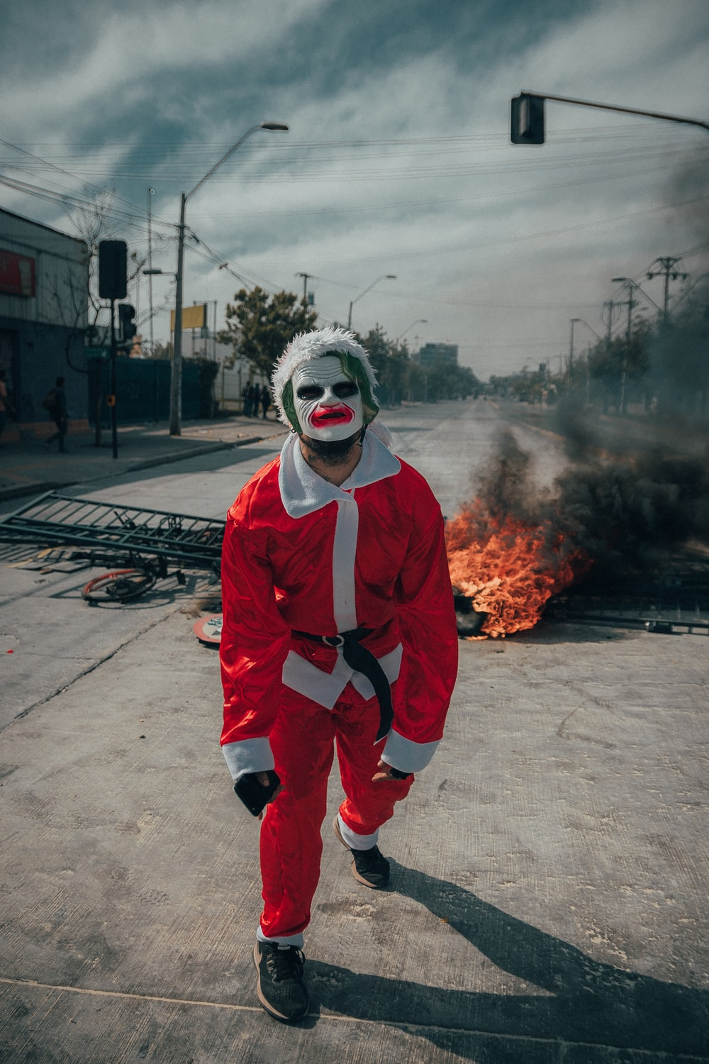 man wearing Santa's costume near burning object