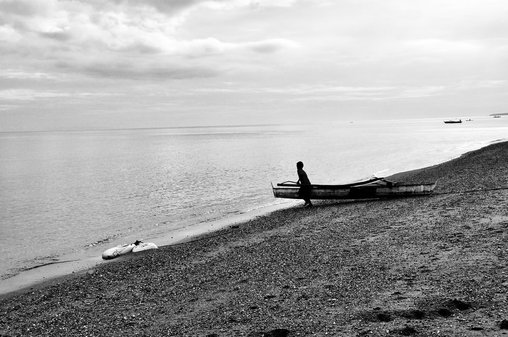 silhouette photography of person standing beside white boat near in front of the ocean