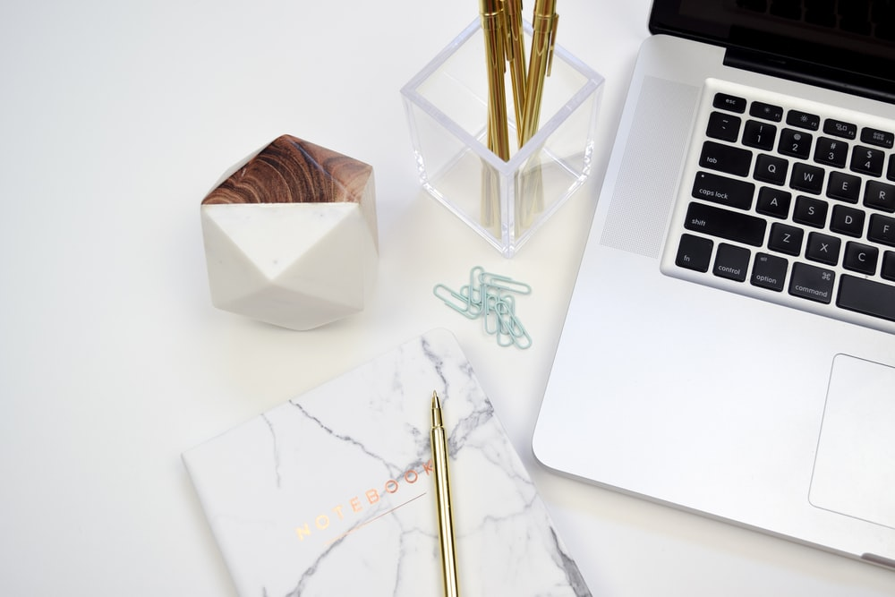 gold pen on white book beside MacBook Pro