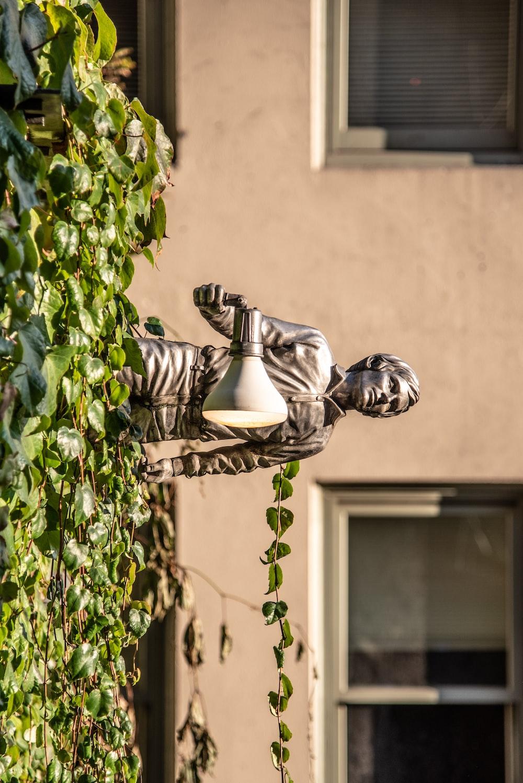 statue man holding light near building