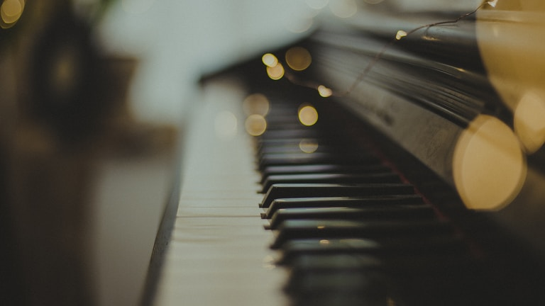 selective focus photography of black wooden piano keys