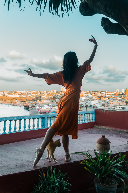 woman in orange dress doing a ballerina stance