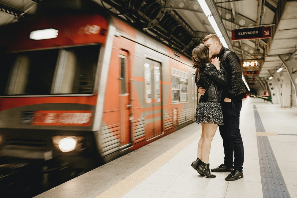 man and woman kissing beside train
