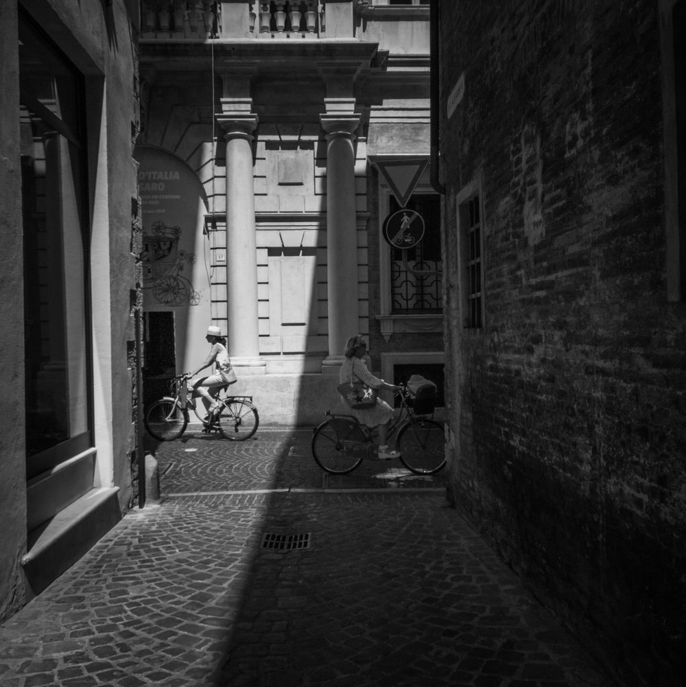 grayscale photography of people cycling during daytime