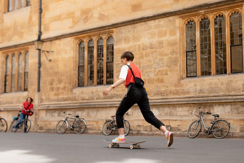 woman skateboarding beside wall