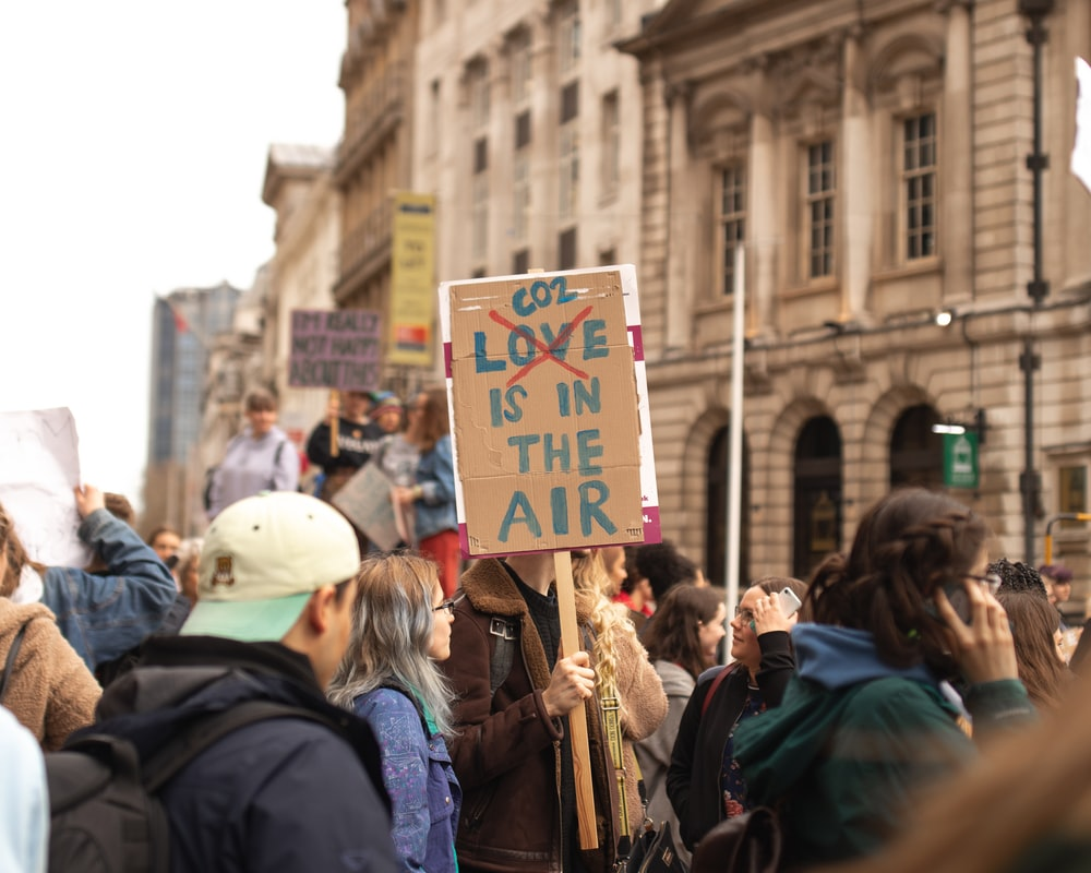 person holding co2 love is in the air signage: climate action