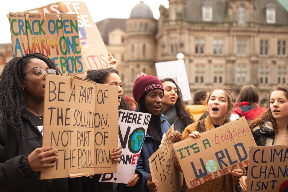 women holding signs during daytime