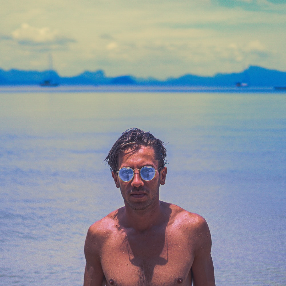 man in gold-colored sunglasses behind sea