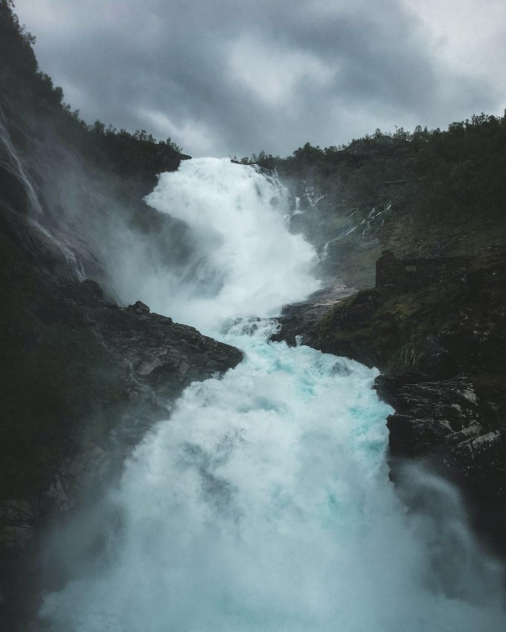 waterfalls under grey sky