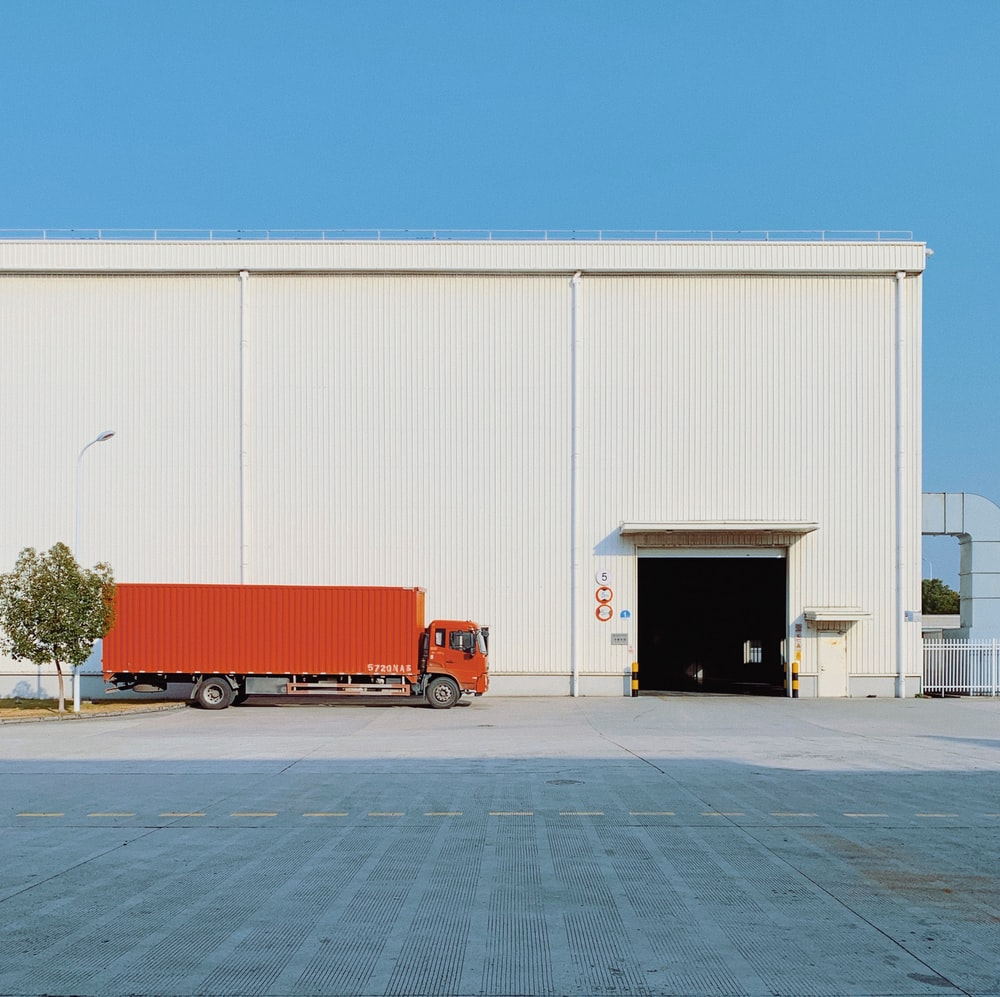 red freight truck beside building