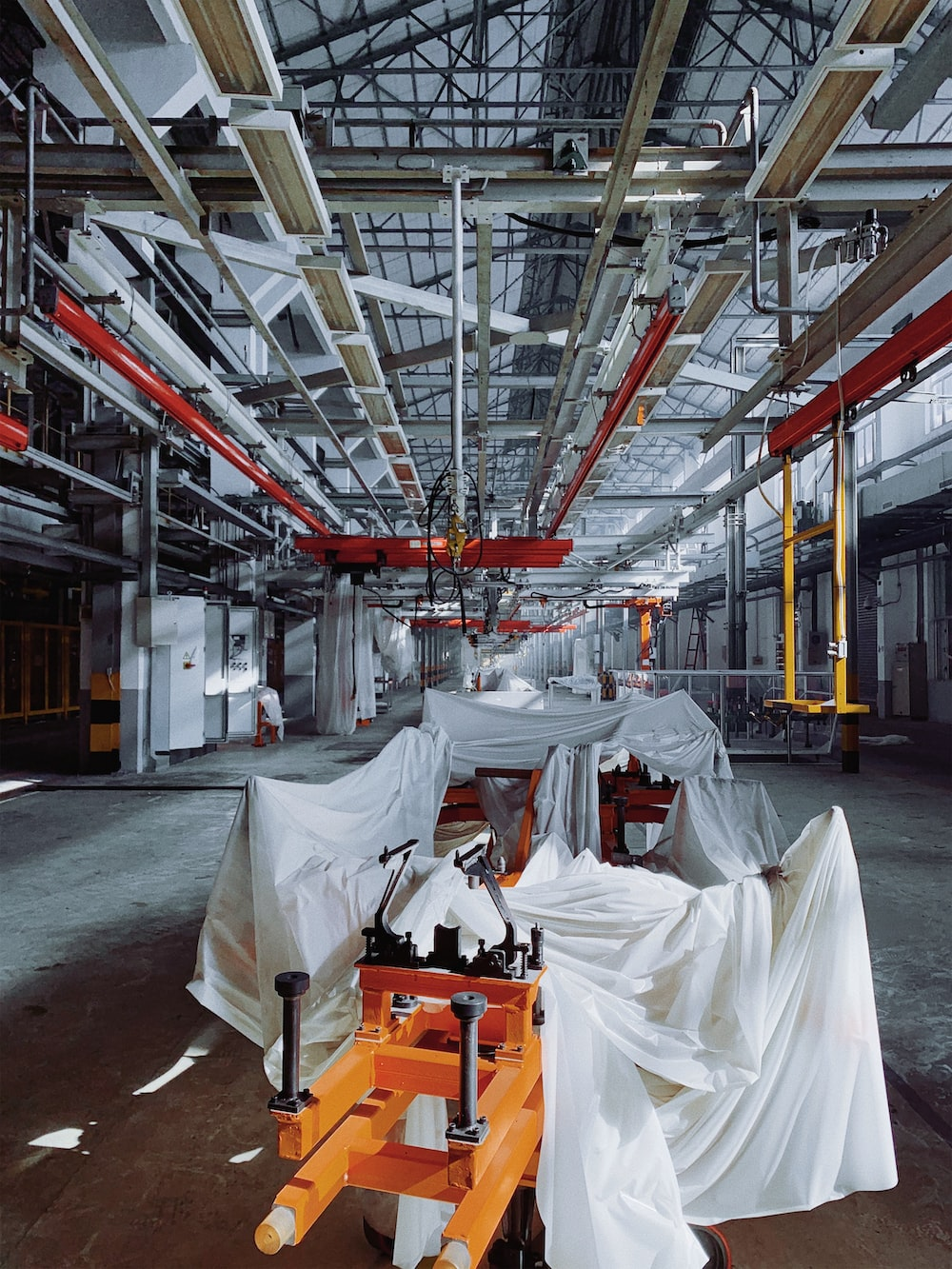 orange industrial machine covered with white textiles