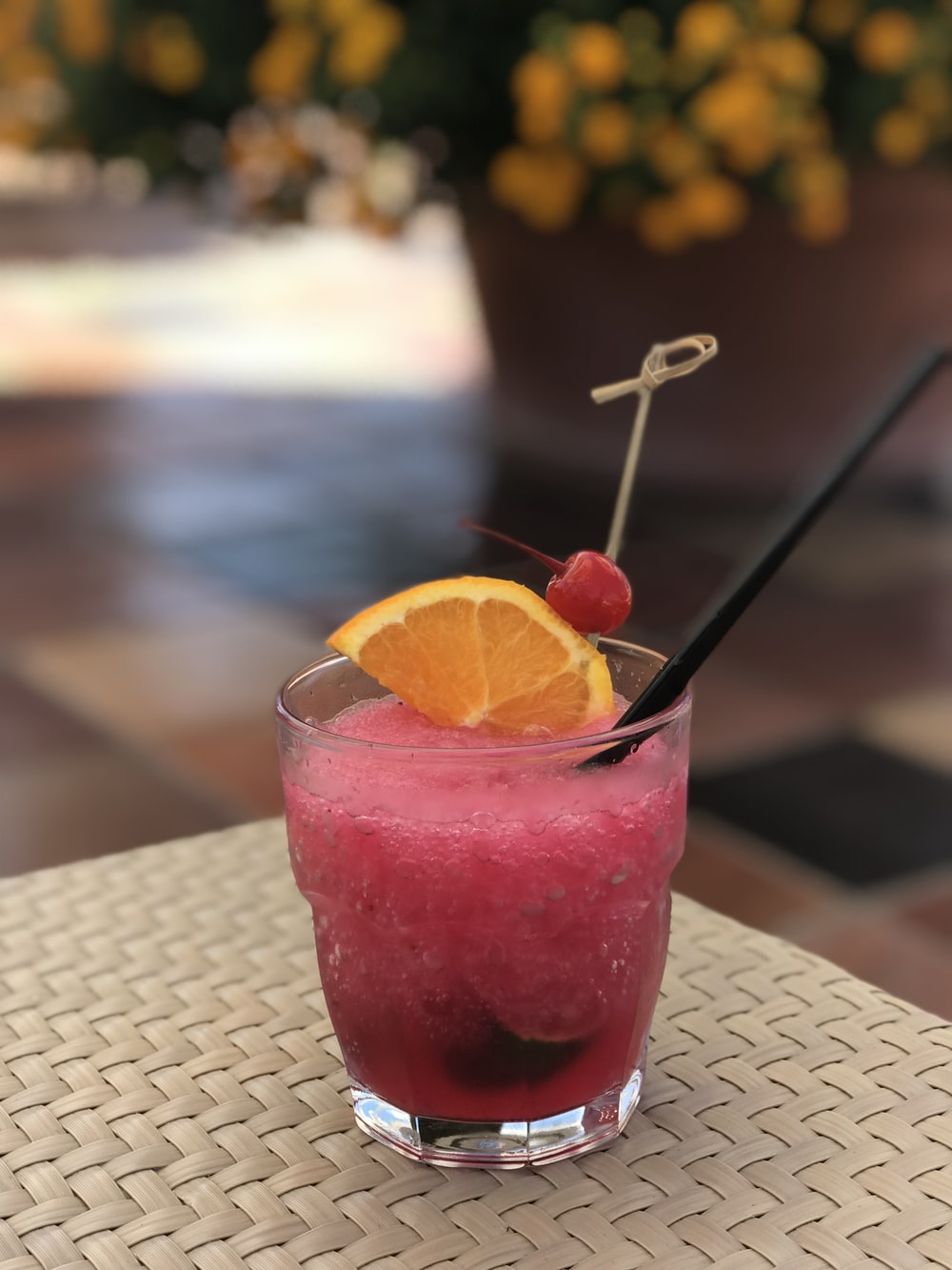 clear drinking glass with pink liquid and sliced orange fruit