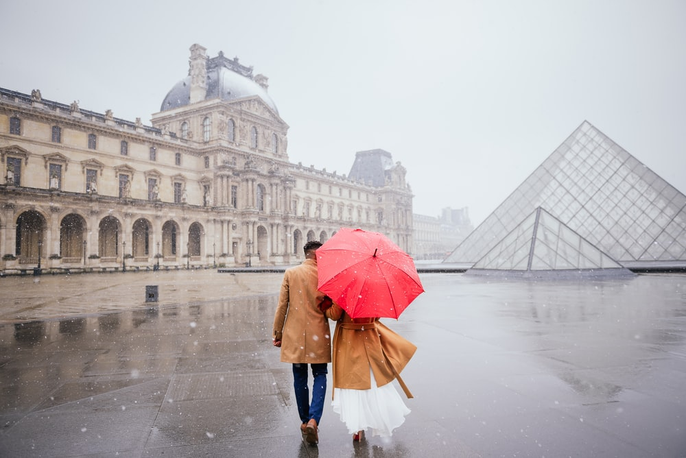 man and woman holding red umbrella