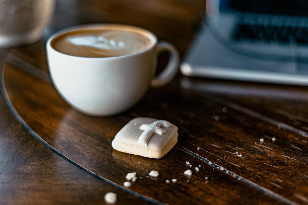 white ceramic teacup beside the laptop