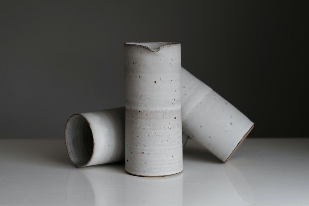 three white enamel jars