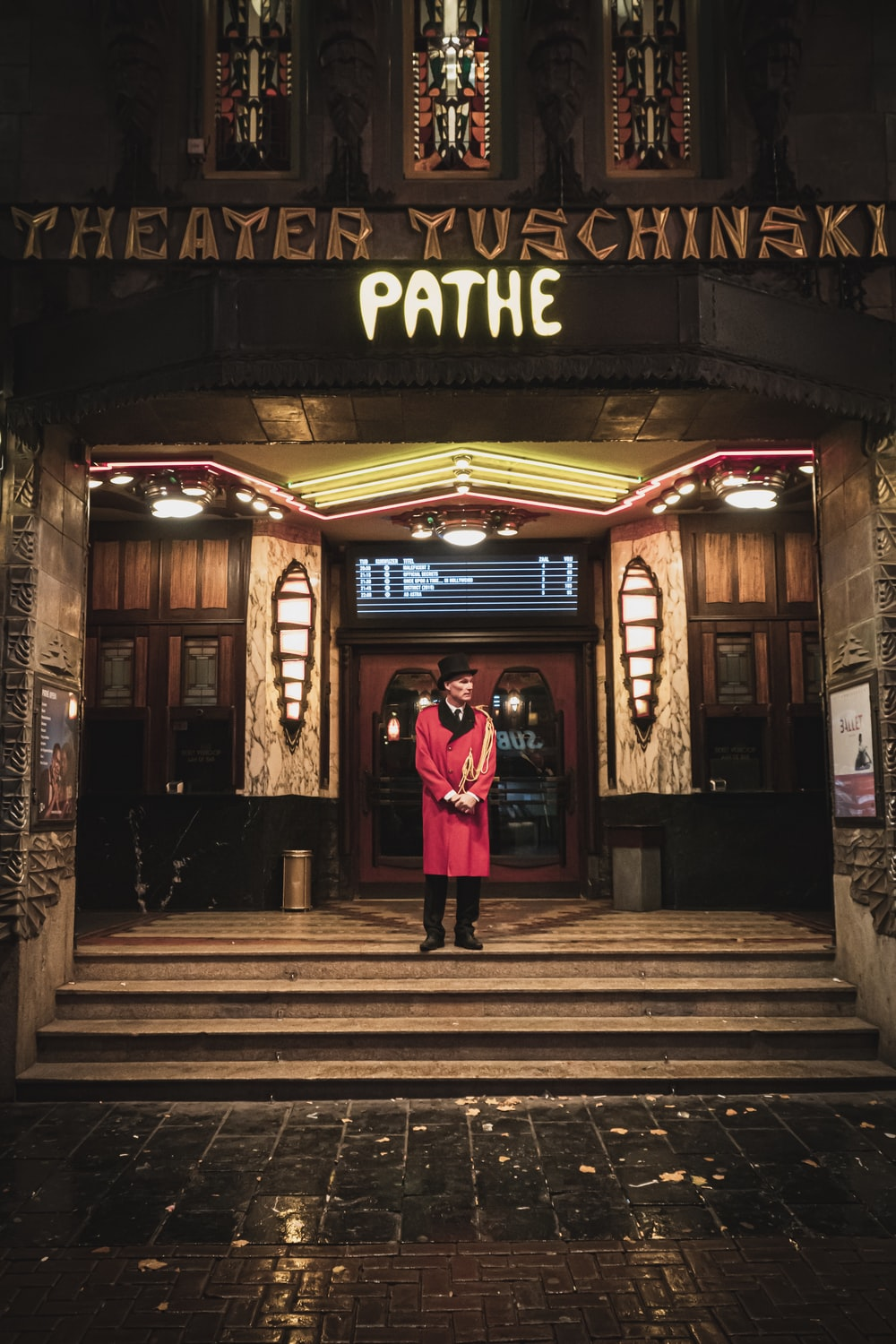 man in red cardigan standing in front of Pathe building